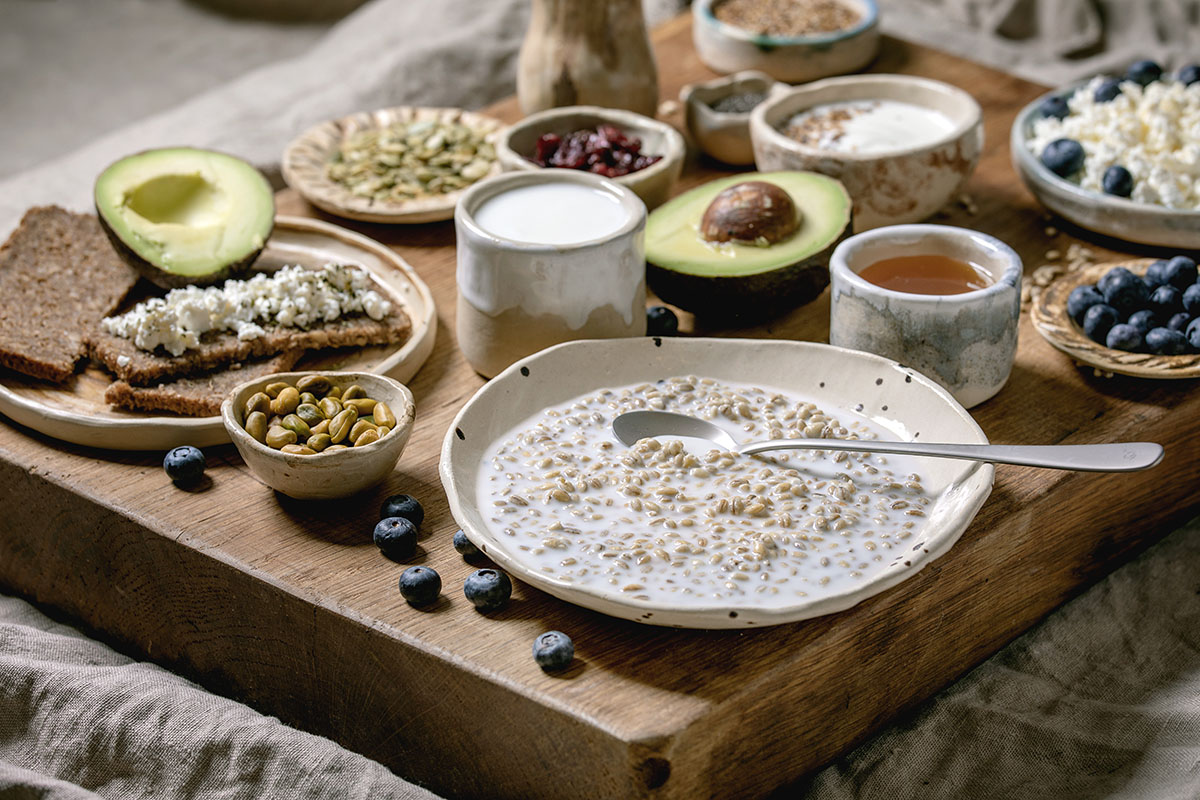 Healthy breakfast. Variety of breakfast dishes sprouted wheat, yogurt, kefir, cottage cheese, avocado, rye bread, seeds, nuts and berries assortment in ceramic bowls over wooden serving board.